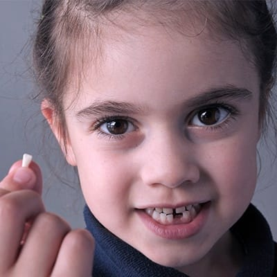 Little girl holding up her tooth