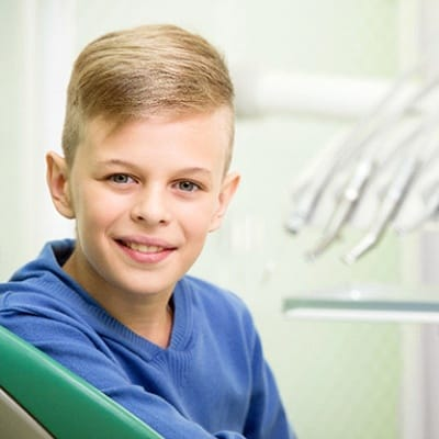 A young boy smiling with dental tools in the background