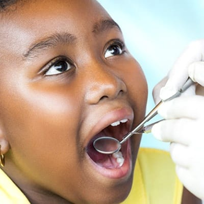 A young girl having her teeth checked