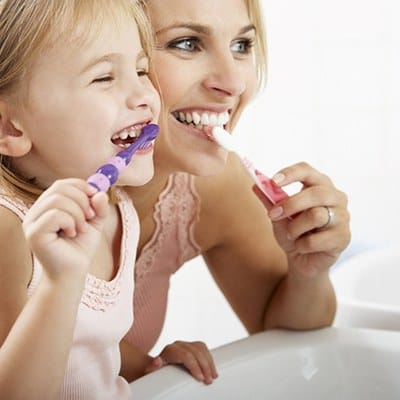 A little girl and her mother standing in front of the sink and brushing their teeth together
