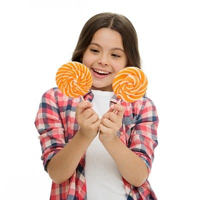 A young girl wearing a plaid shirt and holding two large lollipops while she smiles