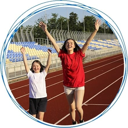Two young girls running on a track