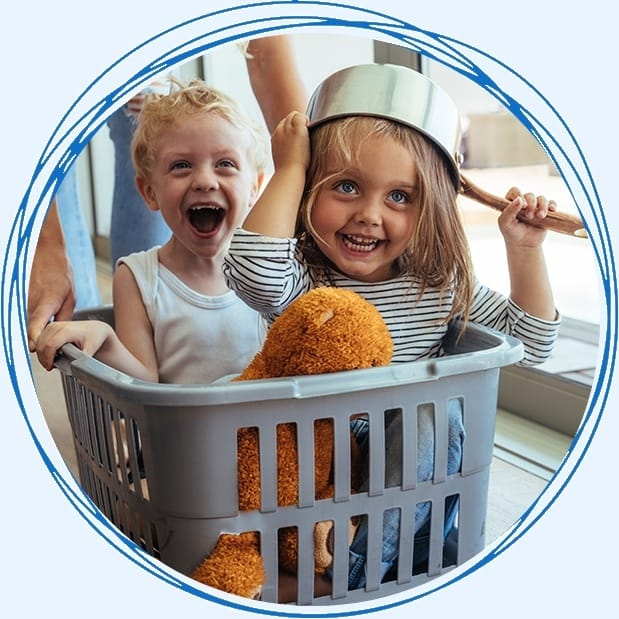 Two young children laughing in laundry basket