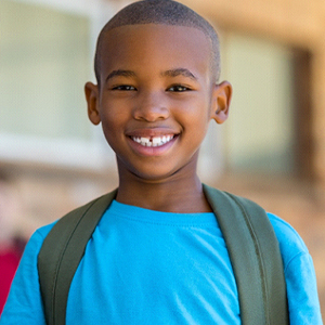 A little boy wearing a blue shirt and backpack smiling while at school