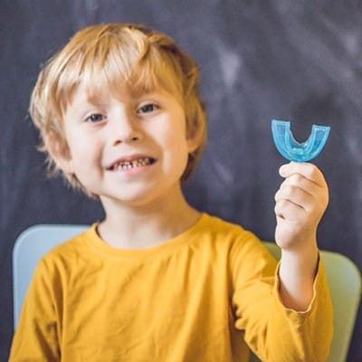 A young boy smiling and holding a blue mouthguard
