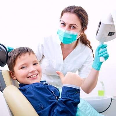 A young boy giving a thumbs up as his dentist looks on behind a mask