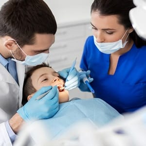 A dentist and dental hygienist examining a young boy's teeth and gums