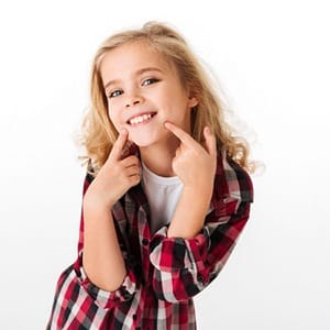 A young girl smiling and pointing to her mouth
