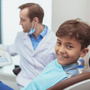 A young boy sitting in the dentist chair smiling