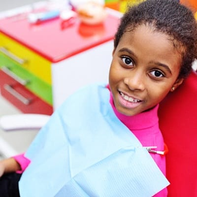 A young girl smiling in the dentist chair