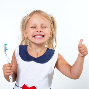 A little girl with blonde hair smiling and giving a thumbs-up while holding a toothbrush after receiving fluoride treatment for kids in McKinney