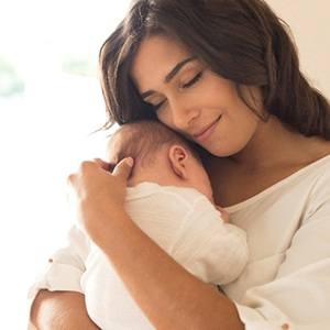 A mother holding her baby close to her chest after a successful breastfeeding session
