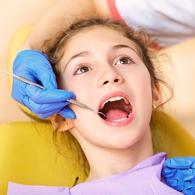 Teen girl receiving dental exam