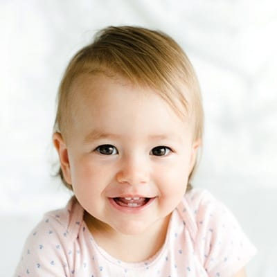 A baby smiling with two top and two bottom teeth showing