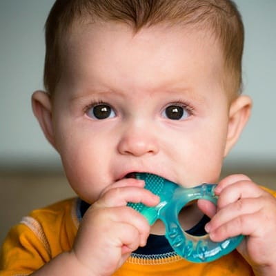 A baby chewing on a teether