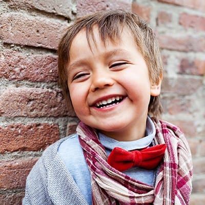 Laughing little boy with red bowtie