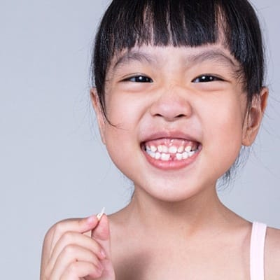 A young girl smiling with a missing tooth
