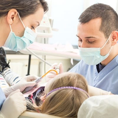 Two dentists performing dental work on a young girl's mouth