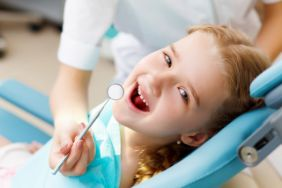 Happy little girl getting a dental exam