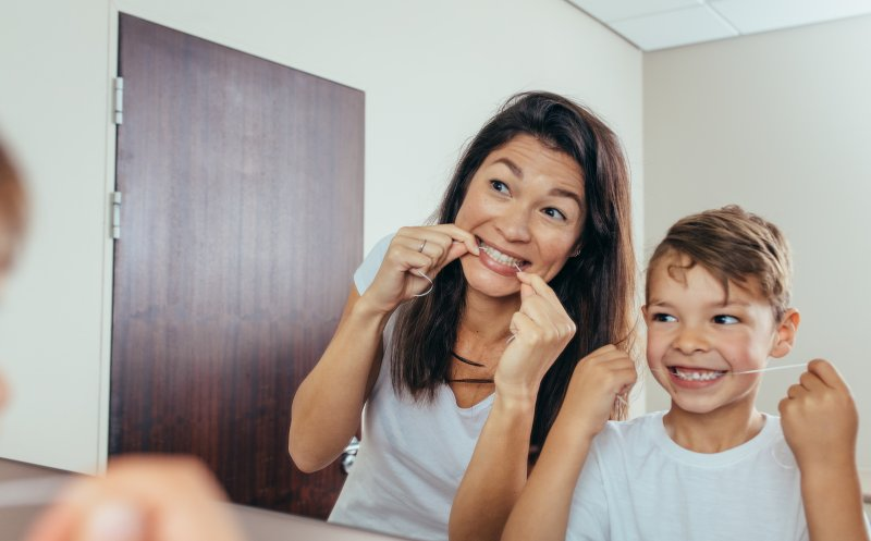 a young boy and his mother flossing their teeth