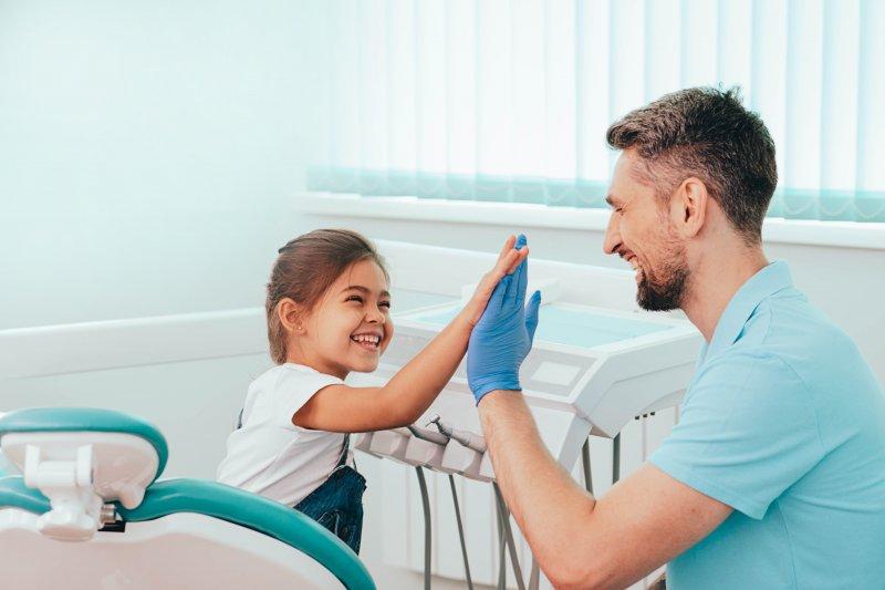 a little girl giving her dentist a high-five