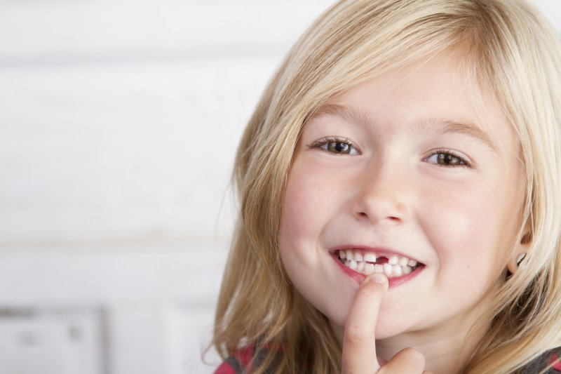 a little girl with a missing tooth