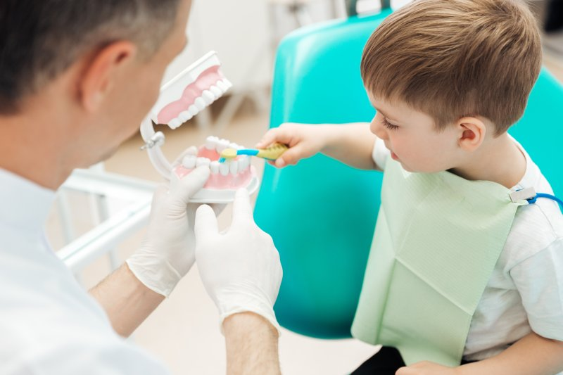 a little boy brushing the teeth of a mouth mold while a dentist instructs him on how to do it properly