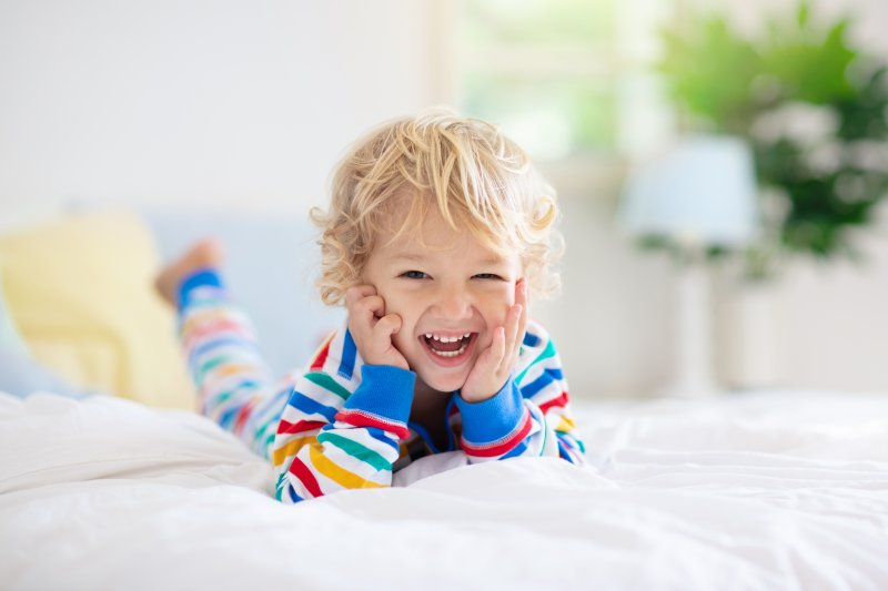 a young child lying on their stomach on a bed and smiling