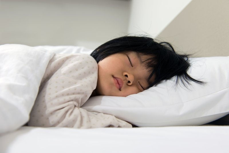 a young child asleep lying on their stomach with their head on a pillow