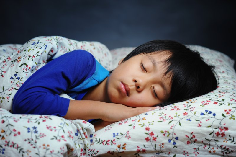 A young boy asleep in bed while lying on his side
