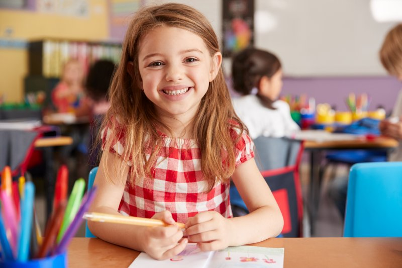 a little girl smiling while seated at her desk at school