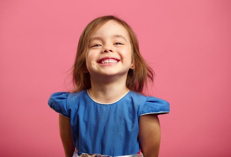 a little girl wearing a blue dress and smiling wide