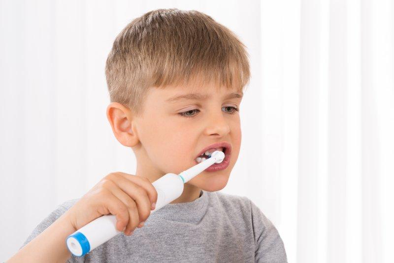 boy using an electric toothbrush